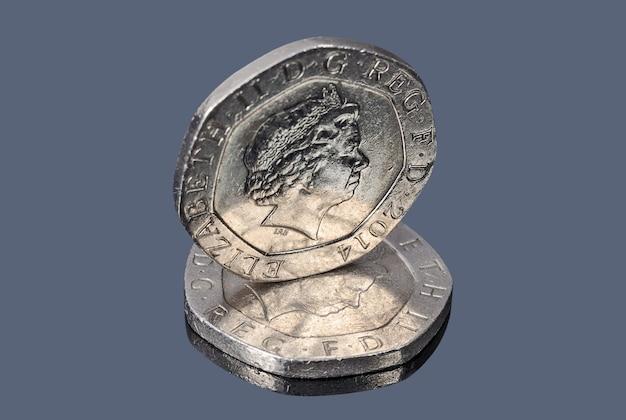 Monedas de veinte peniques británicos en el fondo oscuro