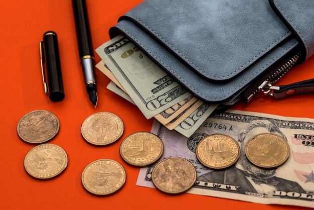 Un monedero de un dólar, monedas y un bolígrafo.