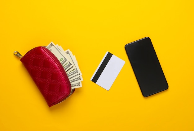 Monedero rojo con billetes de cien dólares, tarjeta bancaria, smartphone en amarillo.