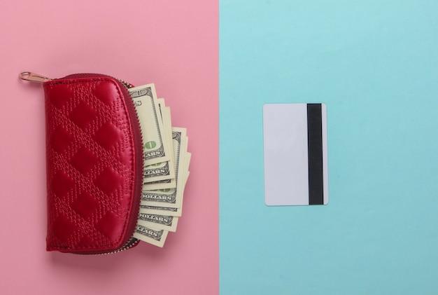 Monedero rojo con billetes de cien dólares y tarjeta bancaria sobre un pastel azul-rosa.