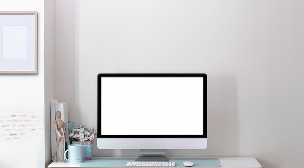Monitor de computadora de pantalla en blanco de maqueta en mesa de madera en habitación moderna con pared de ladrillo.