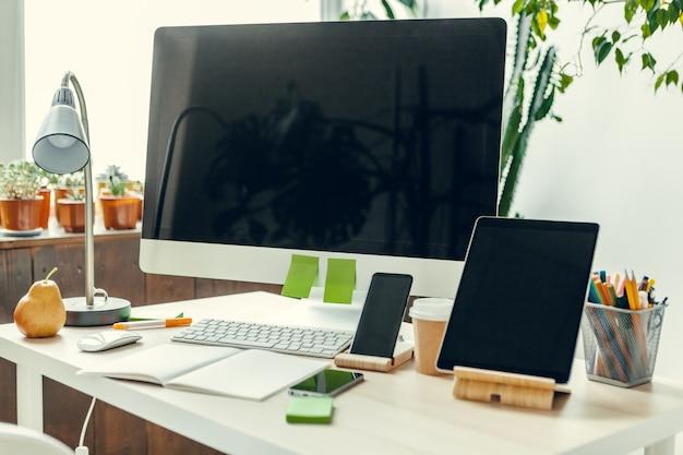 Monitor de computadora con pantalla negra en la mesa de oficina con suministros