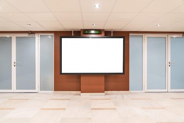 Monitor grande en blanco en lugar público. maqueta de cartelera cerca de las puertas en el centro comercial, terminal del aeropuerto, edificio de oficinas para que mucha gente pueda ver