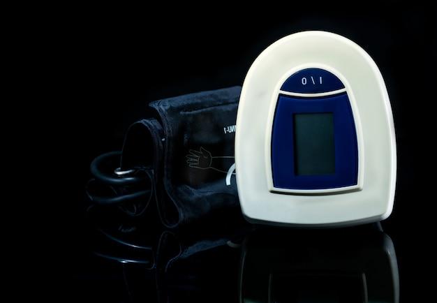 Monitor de presión arterial digital azul-blanco con brazalete de amplio rango aislado sobre fondo oscuro. concepto de chequeo de salud