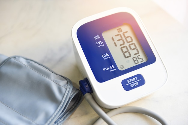 Monitor de presión arterial digital sobre mesa de madera, tonómetro electrónico médico para controlar la presión arterial