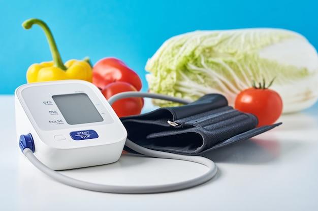 Monitor de presión arterial digital y verduras frescas en la mesa contra azul.