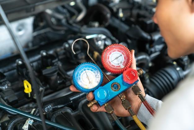 Monitorear la herramienta en el motor del auto, lista para revisar y reparar el sistema de aire acondicionado en el garaje