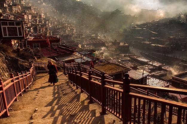 Monja budista caminando por la escalera en larung gar en un momento cálido y con niebla por la mañana, sichuan