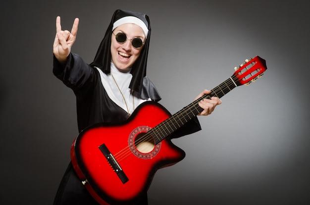 Monja divertida con guitarra roja tocando.