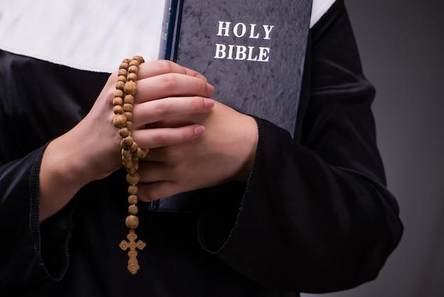 Monja religiosa en concepto de religión contra el fondo oscuro