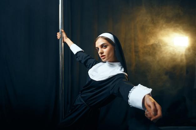 Monja sexy perversa en sotana baila en un poste como una stripper, deseos viciosos. hermana corrupta en el monasterio, gente religiosa pecadora, pecadora atractiva