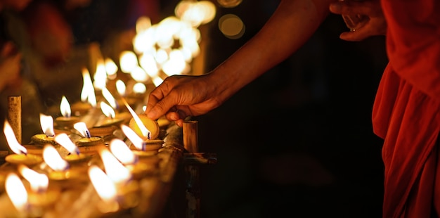 Monje budista manos sosteniendo vela taza en la oscuridad, chiang mai, tailandia