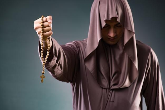 Monje en concepto religioso sobre fondo gris