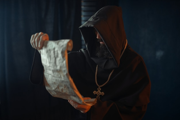 Monje medieval con rostro malvado lee una oración