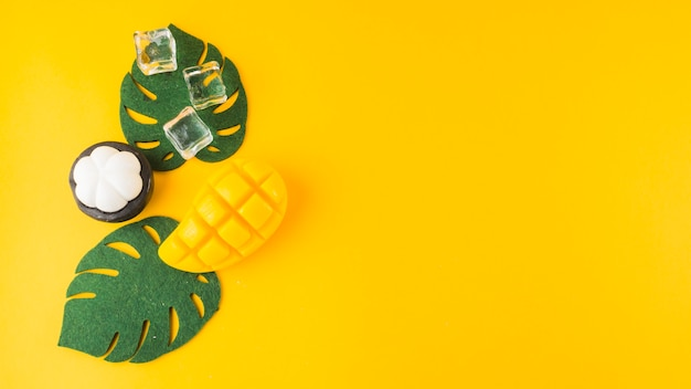 Una monstera artificial deja; mangostán cubitos de hielo y rebanada de mongo contra fondo amarillo
