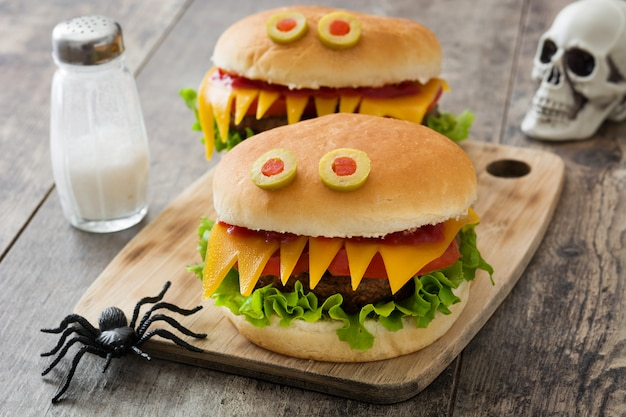Monstruos de hamburguesas de halloween en mesa de madera