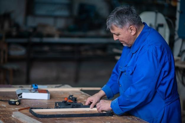 Montaje del marco de madera en la mesa de carpintería en taller con pegamento y diferentes herramientas.