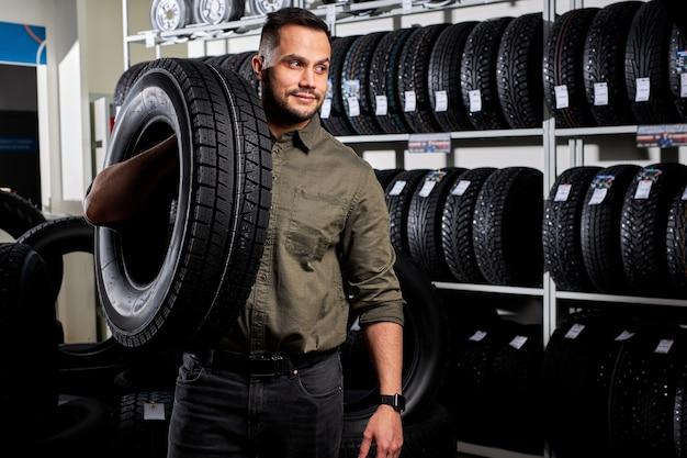 Montaje de neumáticos del cliente en el servicio de automóviles, el mecánico de automóviles comprueba la seguridad del neumático y la banda de rodadura de goma, concepto: reparación de máquinas, diagnóstico de fallas, reparación. hombre compra en tienda de servicio de coche