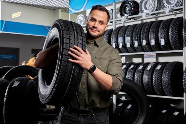 Montaje de neumáticos del cliente en el servicio de automóviles, el mecánico comprueba la seguridad del neumático y la banda de rodadura de goma, concepto: reparación de máquinas, diagnóstico de fallas, reparación hombre comprar en la tienda de servicio de automóviles
