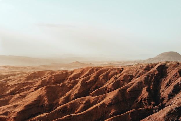 Montaña marrón bajo un cielo blanco durante el día