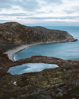 Montaña marrón y verde al lado del cuerpo de agua durante el día