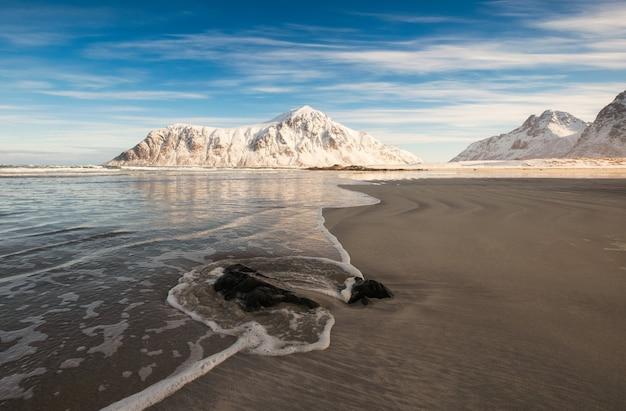 Montaña nevada con ola en la playa en la mañana