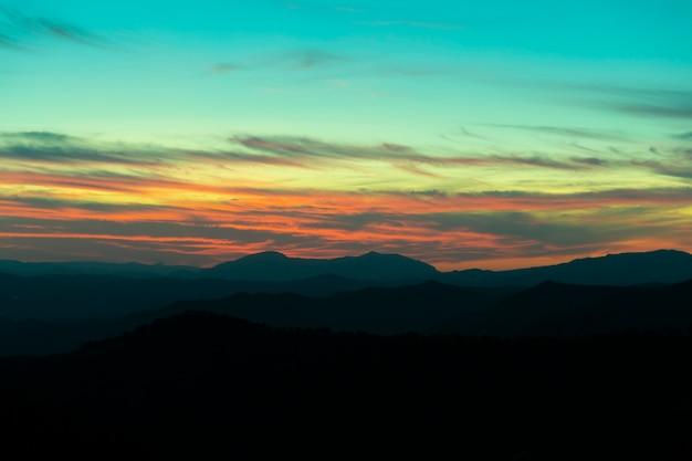 Montaña panorámica y dramático fondo de puesta de sol del cielo