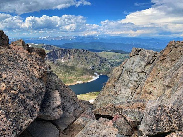 Montaña rocosa gris cerca del lago bajo un cielo azul durante el día