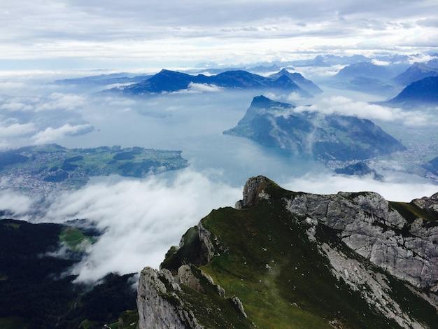 Montaña verde y negra bajo nubes blancas durante el día