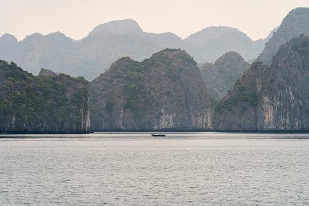 Montañas de la bahía de halong con un bote en el agua