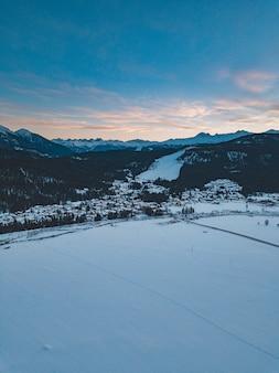 Montañas cubiertas de árboles y nieve durante la puesta de sol por la noche