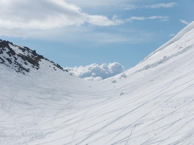 Montañas cubiertas de nieve y las huellas de los cielos y el cielo brillante.