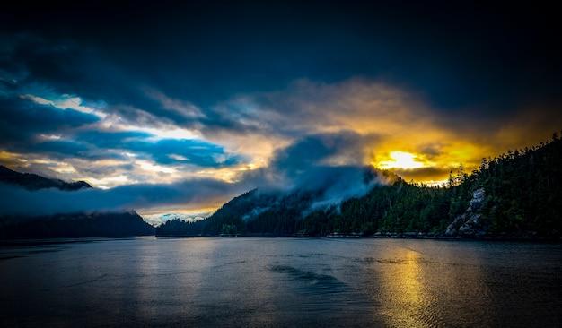 Montañas con fondo de niebla y puesta de sol en el océano de alaska