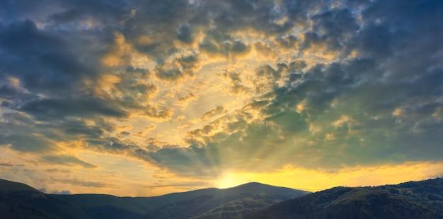 Montañas con hermosa puesta de sol con el brillante sol poniente rompiendo las nubes
