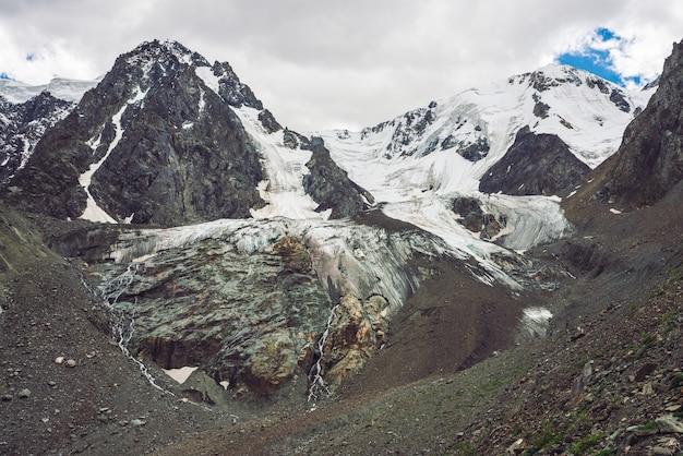 Montañas nevadas gigantes atmosféricas. rocas heladas con cascada. corriente de agua del glaciar. oscura ladera rocosa con hielo. nieve en la cresta de la montaña. paisaje inusual de naturaleza majestuosa de las tierras altas.
