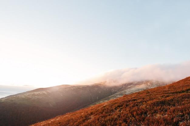 Montañas en la niebla y el amanecer de la mañana