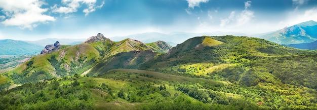 Montañas verdes cubiertas de bosque en el fondo del cielo azul. panorama
