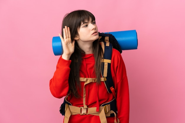 Montañero chica ucraniana con una gran mochila aislada en la pared rosa escuchando algo