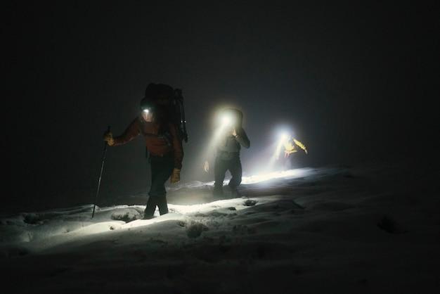 Montañeros trekking en la fría noche en glen coe, escocia