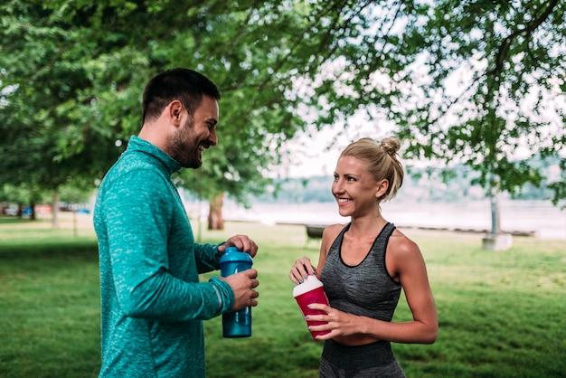 Montar agua potable pareja después del entrenamiento.