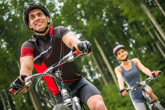 Montar a caballo deportivo joven de los pares en las bicicletas en el camino forestal.