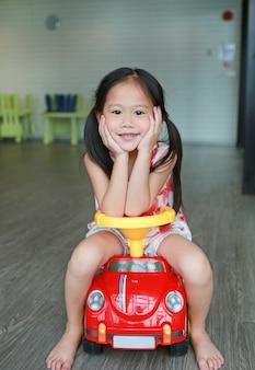 Montar a caballo sonriente de la muchacha del pequeño niño en un pequeño coche en la sala de juegos.