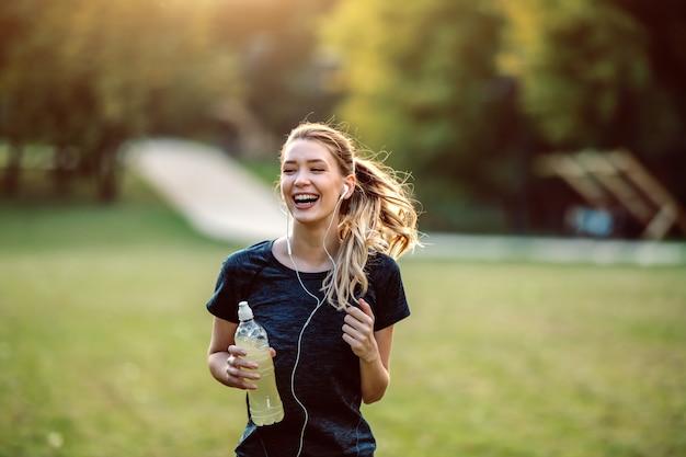 Montar deportista caucásica saludable en ropa deportiva, con cola de caballo y auriculares con refresco en las manos corriendo en la naturaleza.