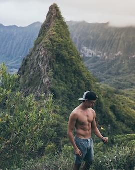Montar excursionista masculino en una gorra en blanco y negro de pie en medio de los campos de hierba en hawai