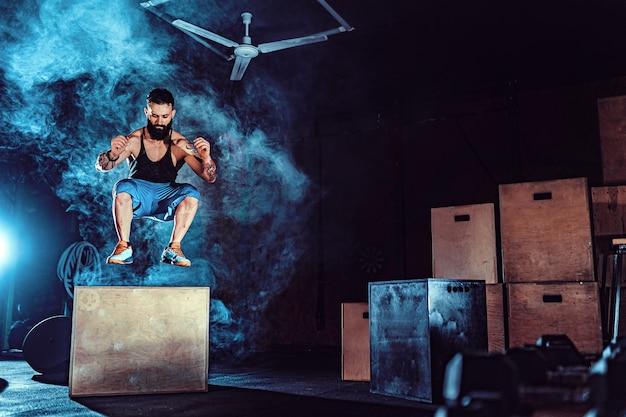 Montar un hombre barbudo tatuado saltando sobre una caja como parte de la rutina de ejercicios. hombre haciendo salto de caja en el gimnasio. el atleta está realizando saltos de caja