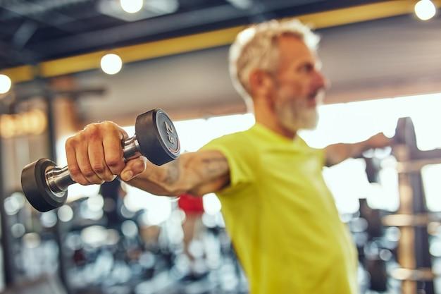 Montar más de cincuenta vista lateral de un hombre caucásico maduro haciendo ejercicio con pesas en el gimnasio se centran en la mano