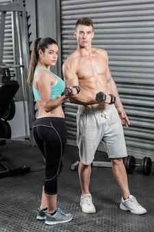 Montar pareja levantando pesas en el gimnasio de crossfit