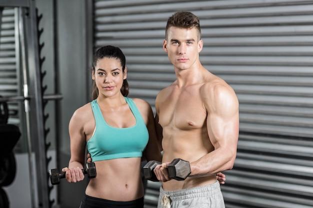 Montar pareja levantando pesas y mirando a la cámara en el gimnasio
