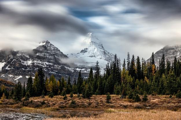 Monte assiniboine con nubes que fluye a través del bosque de otoño en el parque provincial
