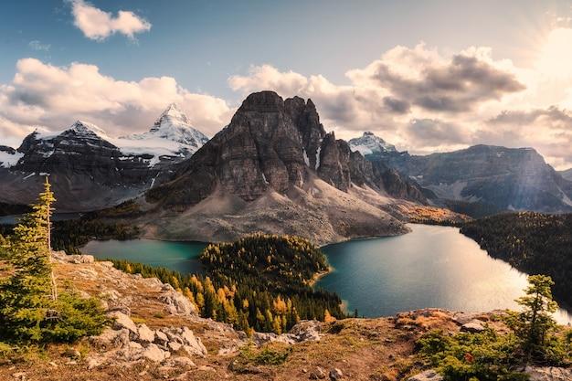 Monte assiniboine con sunburst y lago cerulean en otoño bosque de pinos